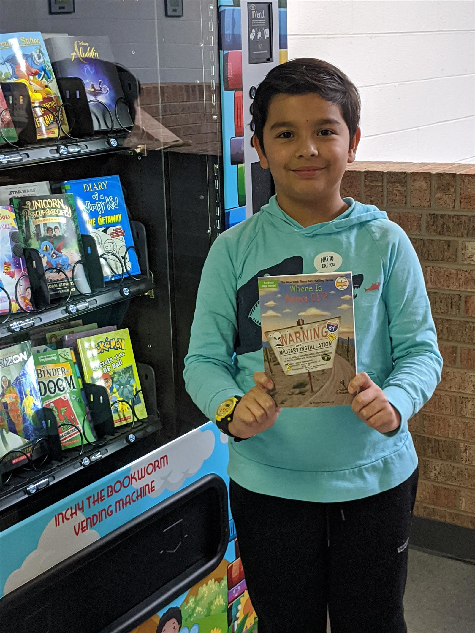 boy holding book by vending machine